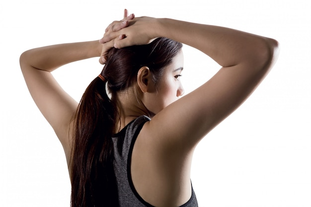 Jeune femme asiatique qui s'étend du corps après la séance d'entraînement sur fond blanc