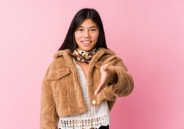 Jeune femme asiatique qui s'étend de la main à la caméra dans le geste de salutation.