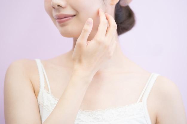 Une jeune femme asiatique qui touche et vérifie son état de peau
