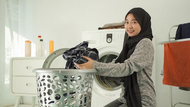 Une jeune femme asiatique ramasse des vêtements sales pour les laver à la maison
