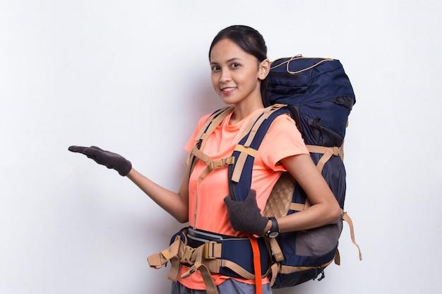 Jeune femme asiatique de randonneur avec le doigt pointé de sac à dos sur l'espace vide sur le fond blanc