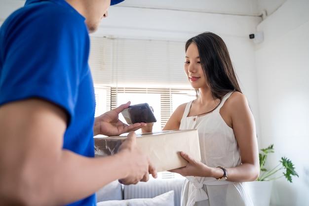 Jeune femme asiatique recevant le colis du livreur. souriant jeune livreur tenant une boîte en carton tandis que belle jeune femme mettant la signature dans le presse-papiers