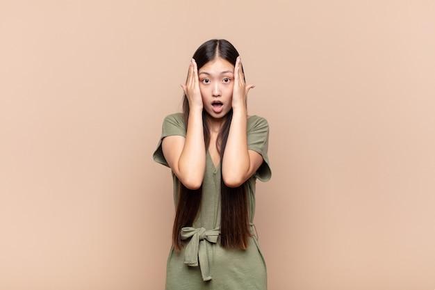 Jeune femme asiatique à la recherche désagréablement choquée, effrayée ou inquiète isolée