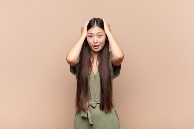 Jeune femme asiatique à la recherche excitée et surprise, bouche bée avec les deux mains sur la tête, se sentant comme un heureux gagnant