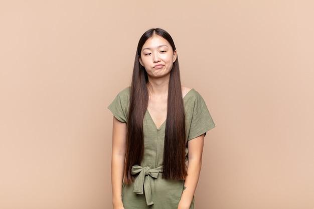 Jeune femme asiatique à la recherche de maladroit et drôle avec une expression idiote aux yeux croisés, plaisanter et s'amuser