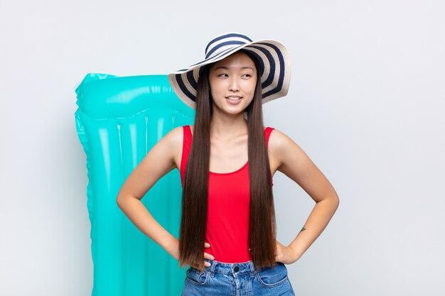 Jeune femme asiatique à la recherche de plaisir, de bonne humeur et confiante, souriant fièrement et à la recherche de l'autre avec les deux mains sur les hanches