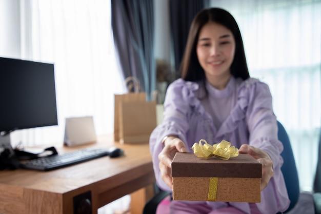 Jeune femme asiatique reçoit une boîte cadeau en une journée spéciale.