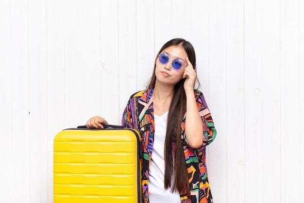 Jeune femme asiatique avec un regard concentré, se demandant avec une expression douteuse isolée