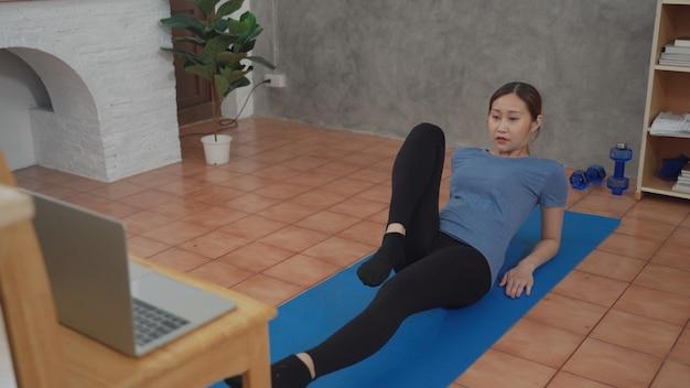 Jeune femme asiatique regardant un didacticiel sur internet en ligne en utilisant un ordinateur portable pour faire de l'exercice et s'entraîner dans le salon de l'appartement. nouvelle norme d'entraînement physique à la maison pendant le confinement