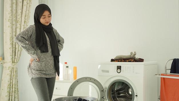 Jeune femme asiatique regardant le panier de vêtements sales à la maison