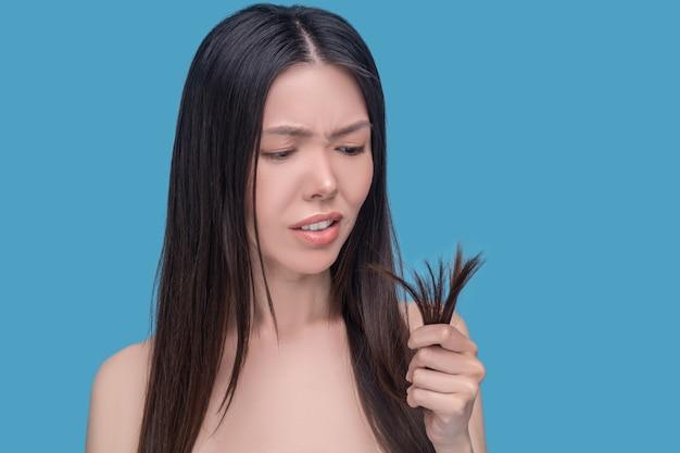 Jeune femme asiatique regardant ses cheveux se termine et se sentant insatisfait
