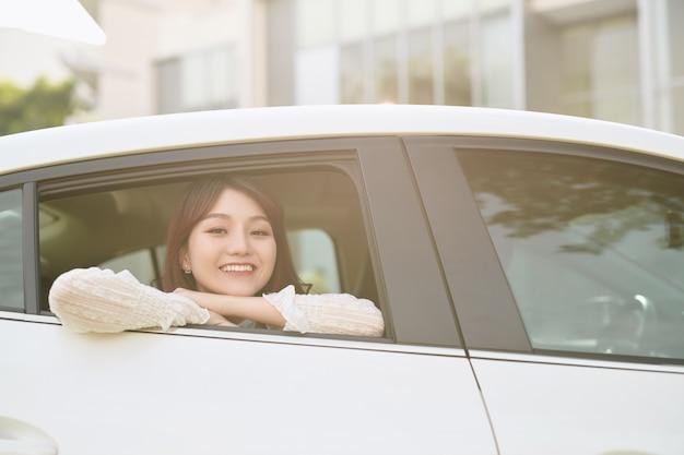 Jeune femme asiatique regarde par la fenêtre de la voiture