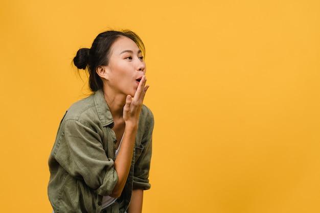 Une jeune femme asiatique ressent du bonheur avec une expression positive, une joyeuse surprise funky, vêtue d'un tissu décontracté isolé sur un mur jaune. heureuse adorable femme heureuse se réjouit du succès. expression du visage.