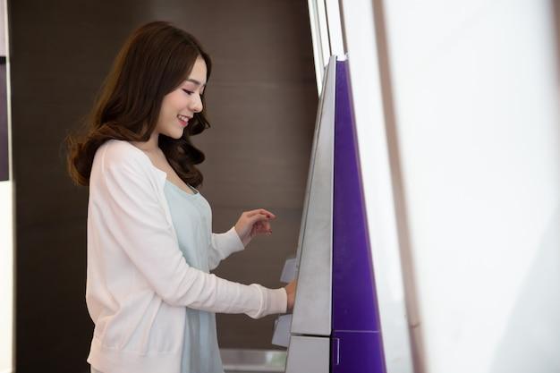 Jeune femme asiatique retirer de l'argent avec une carte à la machine automatique
