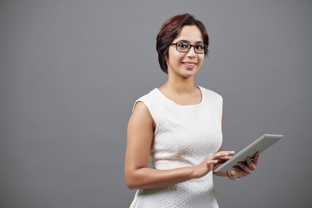 Jeune femme asiatique en robe intelligente qui pose en studio avec tablette