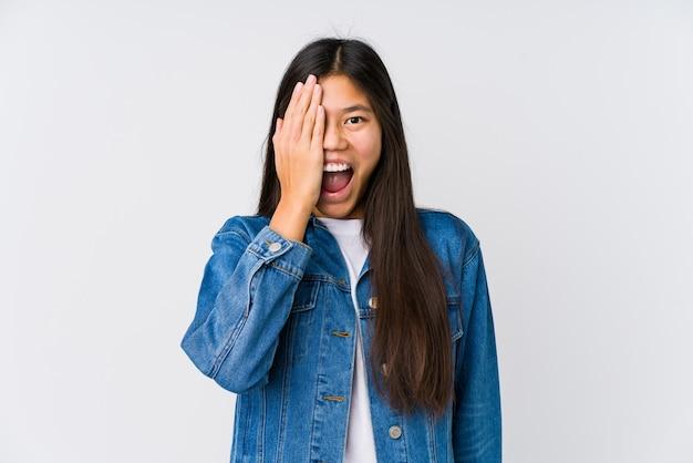 Jeune femme asiatique s'amuser couvrant la moitié du visage avec la paume.