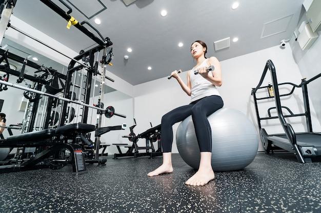 Jeune femme asiatique s'entraînant avec des boules d'équilibre et des haltères