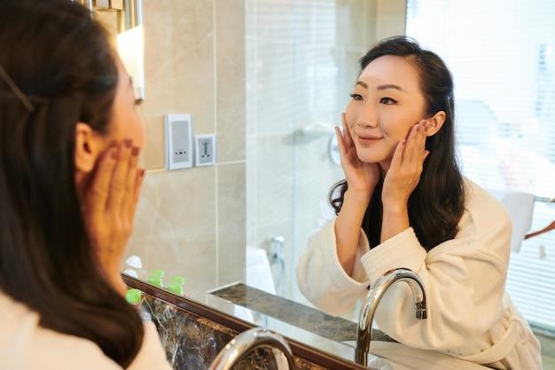 Jeune femme asiatique satisfaite en peignoir debout devant un miroir dans la salle de bain et se lave le visage