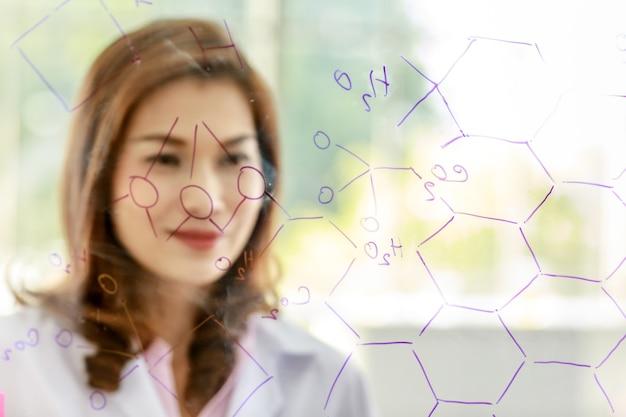 Jeune femme asiatique scientifique en chimie écrivant une formule avec un marqueur sur du verre transparent pendant les travaux de recherche en laboratoire.