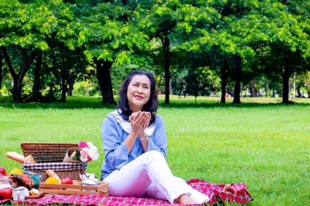 Jeune femme asiatique se détendre dans le parc. le matin elle boit du thé