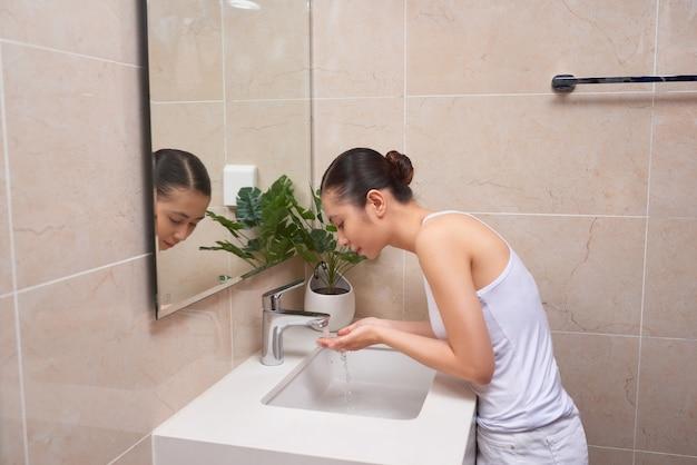 Jeune femme asiatique se lavant le visage sur l'évier