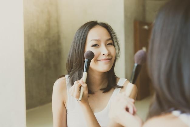 Jeune femme asiatique se maquiller