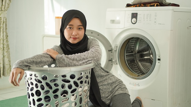 Jeune femme asiatique se prépare à faire la lessive à la maison