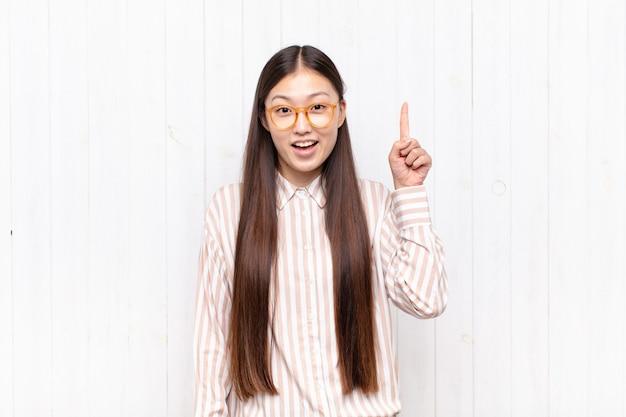 Jeune femme asiatique se sentant comme un génie heureux et excité après avoir réalisé une idée, levant joyeusement le doigt, eureka!