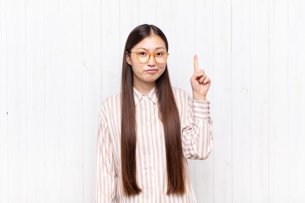 Jeune femme asiatique se sentant comme un génie tenant le doigt fièrement en l'air après avoir réalisé une excellente idée, disant eureka