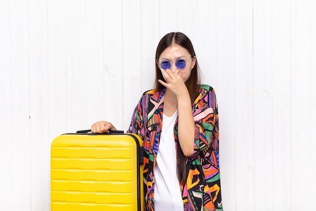 Jeune femme asiatique se sentant dégoûtée, tenant le nez pour éviter de sentir une odeur nauséabonde et désagréable. concept de vacances