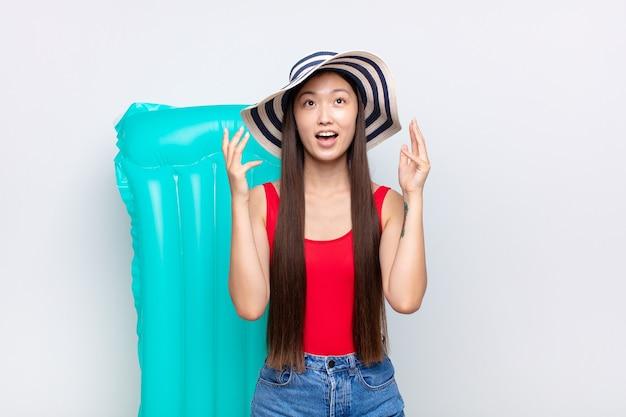 Jeune femme asiatique se sentant heureuse, émerveillée, chanceuse et surprise, célébrant la victoire avec les deux mains en l'air. concept d'été