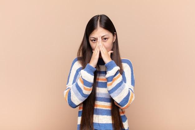 Jeune femme asiatique se sentant inquiète, pleine d'espoir et religieux, priant fidèlement avec les paumes pressées, implorant pardon