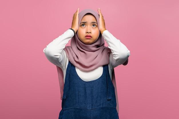 Jeune femme asiatique se sentant mal de tête sur fond rose