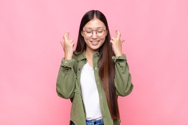 Jeune femme asiatique se sentant nerveuse et pleine d'espoir, croisant les doigts, priant et espérant avoir de la chance
