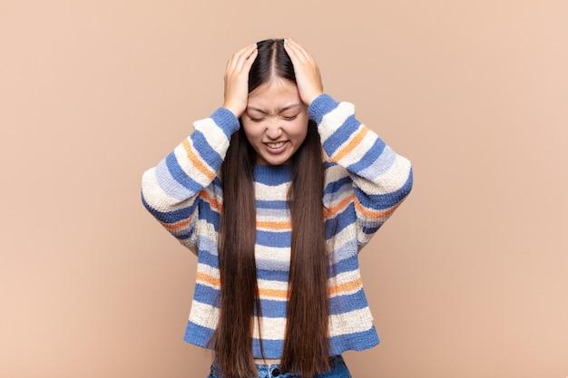 Jeune femme asiatique se sentant stressée et frustrée, levant les mains à la tête, se sentant fatiguée, malheureuse et souffrant de migraine