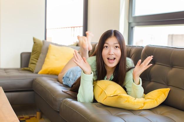 Jeune femme asiatique se sentir heureuse, étonnée, chanceuse et surprise, célébrant la victoire avec les deux mains en l'air