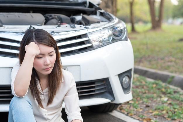 Jeune femme asiatique se sentir triste assis près de la voiture en panne