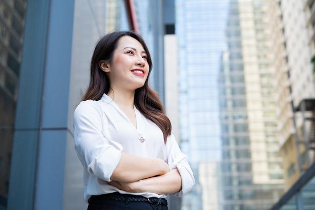 Jeune femme asiatique se tenait les bras croisés avec un regard confiant