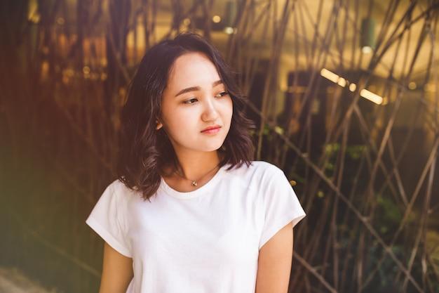 Jeune femme asiatique séduisante dans un t-shirt blanc calme ou triste, pensant à quelque chose et regardant sur le côté.