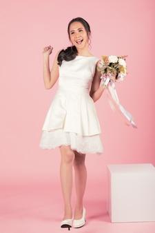 Jeune femme asiatique séduisante portant une robe de mariée blanche tenant un bouquet de fleurs à l'air heureux et joyeux sur fond rose. concept pour la photographie avant le mariage.