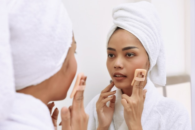Jeune femme asiatique avec des serviettes de bain nettoie son visage
