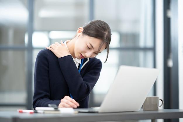 Jeune femme asiatique souffrant d'épaules raides au travail de bureau