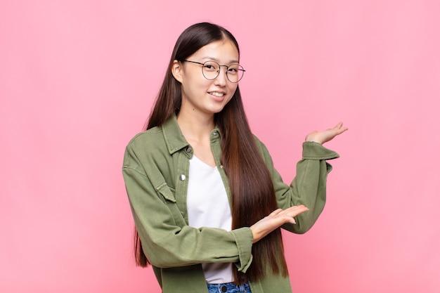 Jeune femme asiatique souriant fièrement et avec confiance, se sentant heureuse et satisfaite