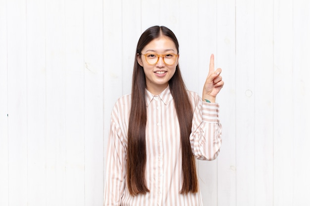 Jeune femme asiatique souriant joyeusement et heureusement isolé