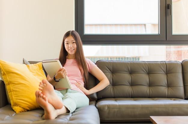 Jeune femme asiatique souriant joyeusement avec une main sur la hanche