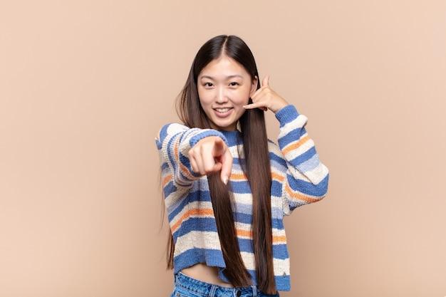 Jeune femme asiatique souriant joyeusement et pointant tout en faisant un appel, vous geste plus tard, parler au téléphone