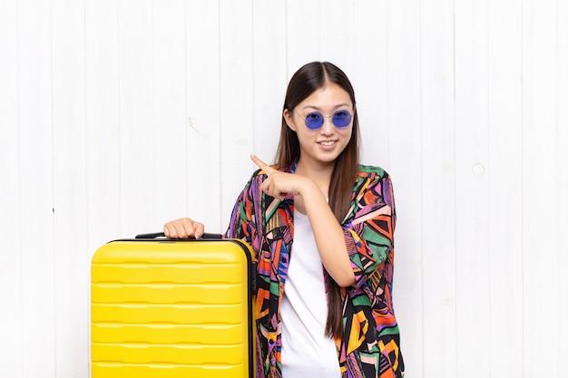Jeune femme asiatique souriant joyeusement et pointant vers l'espace de copie sur la paume sur le côté, montrant ou annonçant un objet. concept de vacances