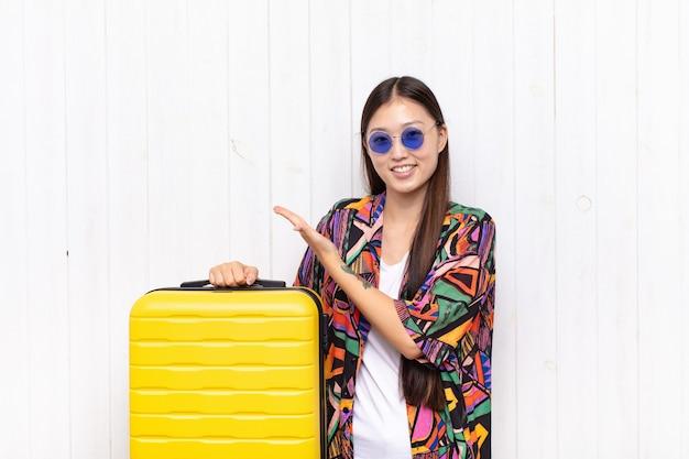 Jeune femme asiatique souriant joyeusement, se sentant heureuse et montrant un concept dans l'espace de copie avec la paume de la main. concept de vacances