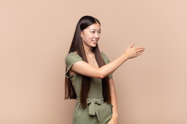 Jeune femme asiatique souriant, vous saluant et offrant une poignée de main pour conclure un accord réussi, concept de coopération