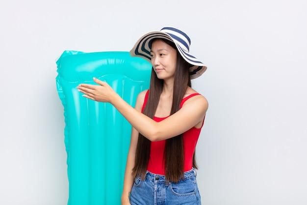 Jeune femme asiatique souriant, vous saluant et offrant une poignée de main